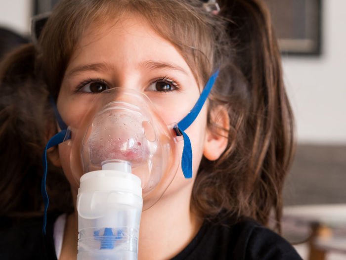 Cute little girl making inhalation with inhaler close up Girl Kid Child Childhood Ill Small Little Cute Caucasian Inhaler Inhaling Inhalation Oxygen Mask Health Medicine Bronchitis Flu Home Close Up Indoors  Asthma Asthmatic Medical Treatment Allergy Patient Care Breath Headshot Close-up Hairstyle
