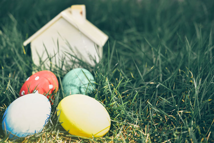 Close-Up Of Multi Colored Easter Eggs With Model Home On Grass