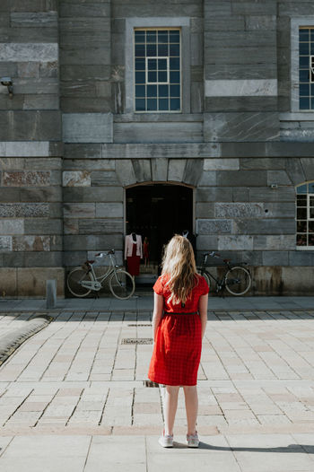 Girl in a red dress Red Red Dress Thinking Architecture Bicycles Blond Hair Building Exterior Built Structure Childhood Contemplative Day Full Length Girl Lifestyles One Person Outdoors Real People Rear View Standing Women