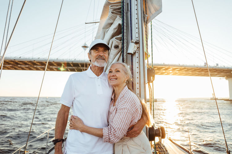 Senior couple on boat at sea against sky