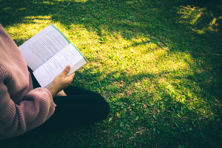 Midsection of woman reading book on field