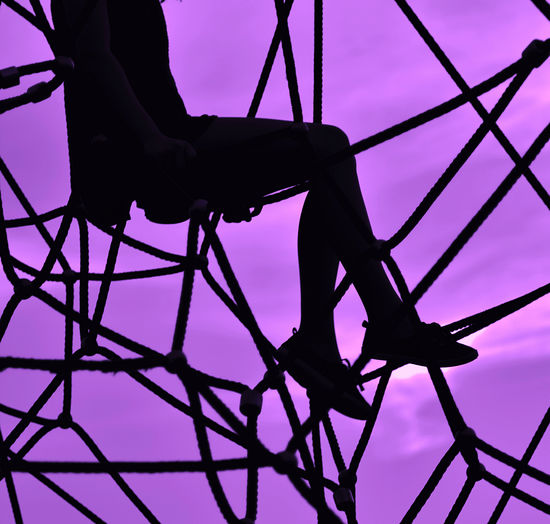 Low angle view of silhouette person on metallic structure against sky