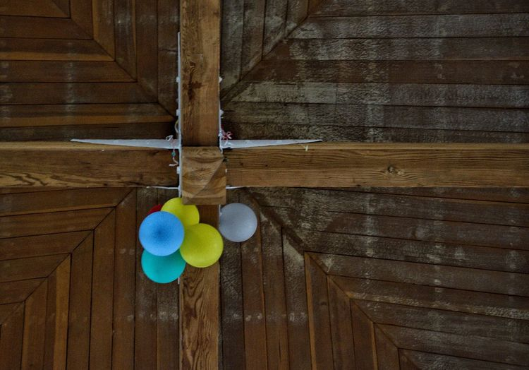 Close-up of multi colored balloons hanging on wood