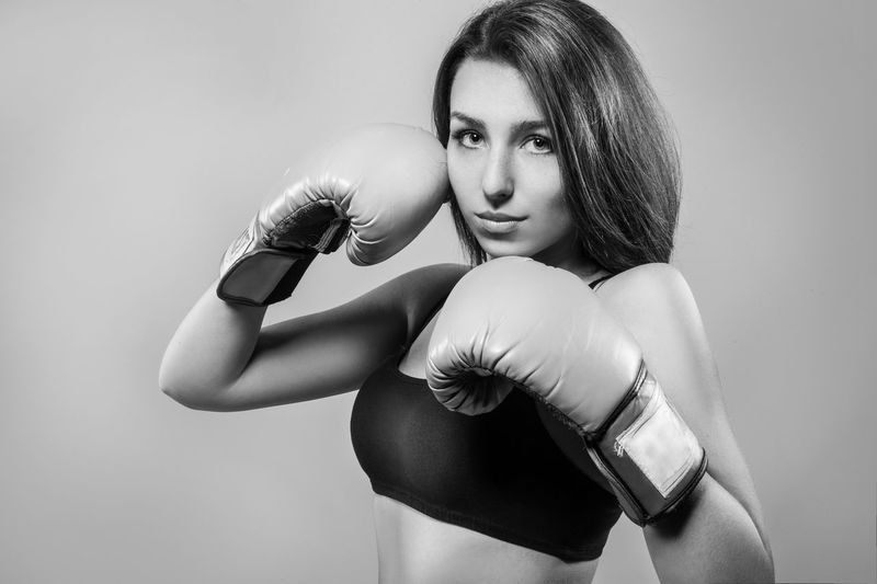 Portrait Of Young Woman In Fighting Stance Over Gray Background