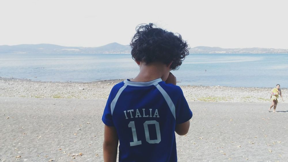 Italia dreaming. Bracciano Lake. Child Water Sky Day Horizon Over Water Standing Outdoors One Person Nature Clear Sky One Boy Only Beauty In Nature Childhood The Week On EyeEm EyeEmNewHere Vacations Afternoonlight Sunnyday☀️ Afternoon Bracciano (Roma) Lake Life Curly Hair Don't Care Portraits PortraitPhotography EyeEm Gallery Focus On The Story World Cup 2018