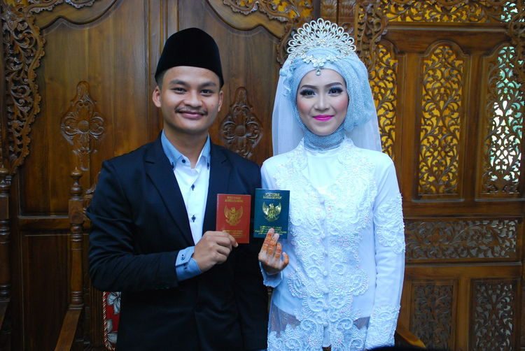 Portrait of bride and bridegroom holding passports while standing against wall