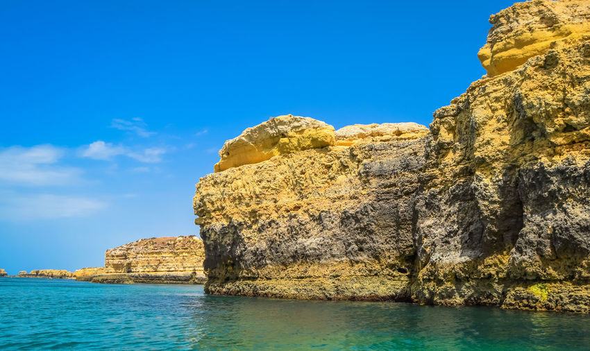 Rock formation by sea against blue sky