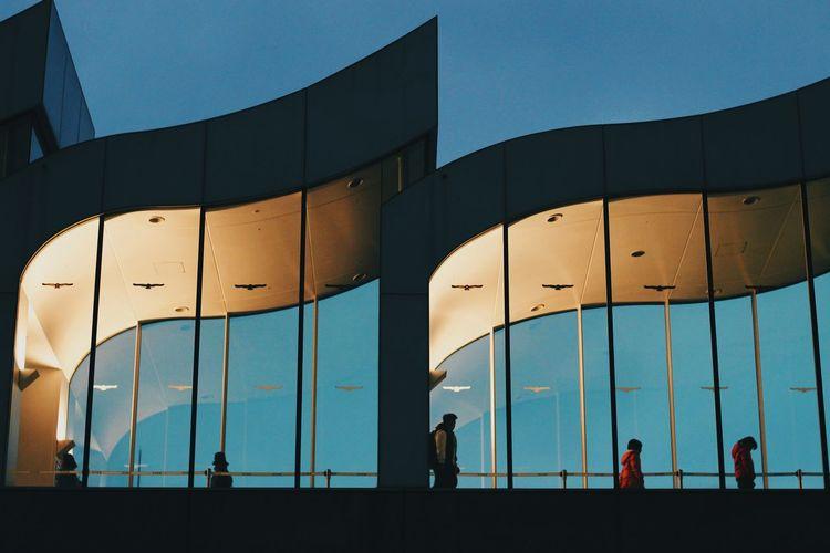 Silhouette people walking on modern building against clear blue sky