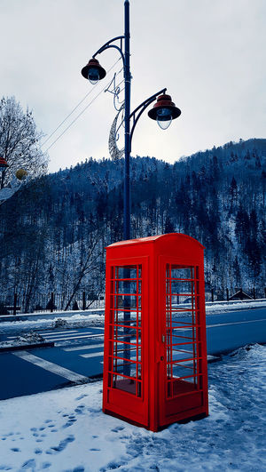 Classic red British telephone box on the snowy street in Sinaia, Carpathian Mountains, Romania EyeEmNewHere Winter Cold Temperature Snow Tree Plant Nature No People Mountain Sky Day Street Technology Beauty In Nature Outdoors Frozen Communication Telephone Booth Field Red Snowcapped Mountain
