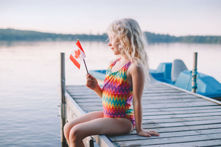 Girl sitting on pier by lake and waving canadian flag. kid celebrating canada day holiday outdoor