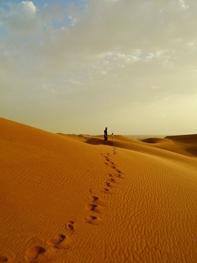 Mid distance view of people on sand dunes at desert against sky during sunset