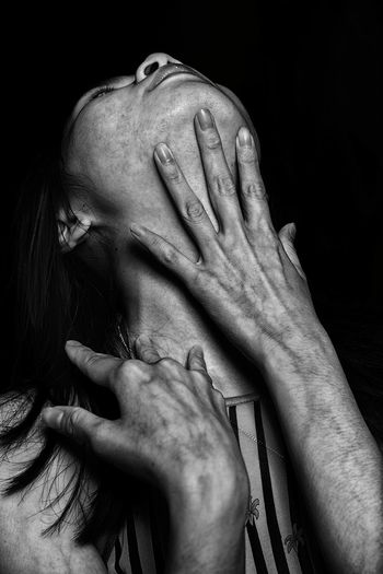 Woman touching neck against black background