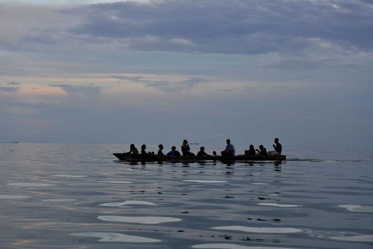 Boats in calm sea against cloudy sky
