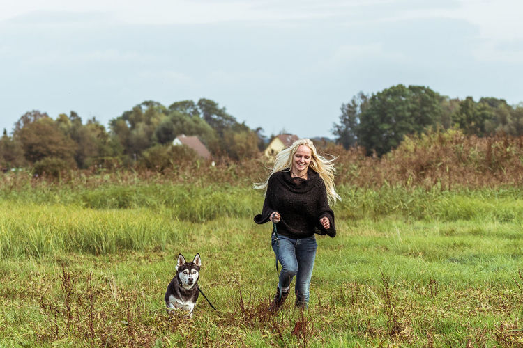 Full Length Of Woman With Dog Running On Field