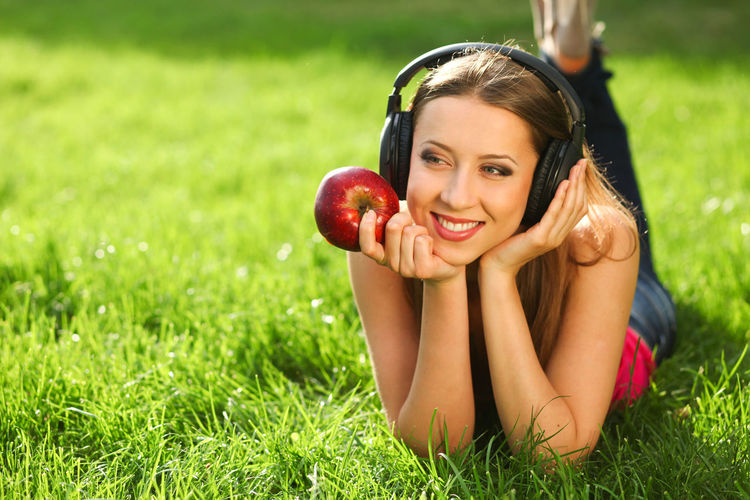 Woman with headphones listening music on the grass Hair Hairstyle Lying Down Adult Young Adult Wellbeing Healthy Eating Food Cheerful Emotion Beautiful Woman Beauty Plant Portrait Apple - Fruit Fruit One Person Women Happiness Smiling Grass Leisure Activity Food And Drink Outdoors