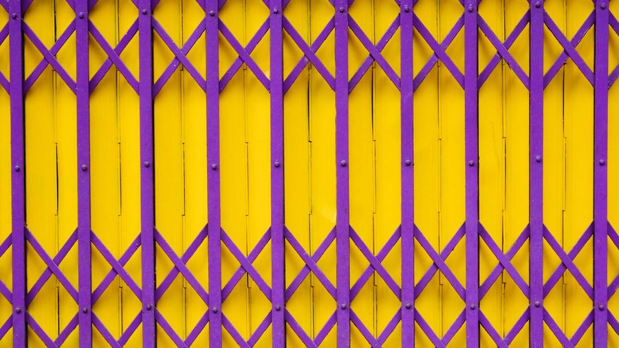Full frame shot of multi colored metal fence against blue wall
