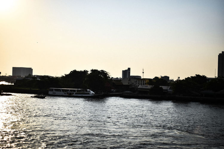 River by buildings against clear sky during sunset