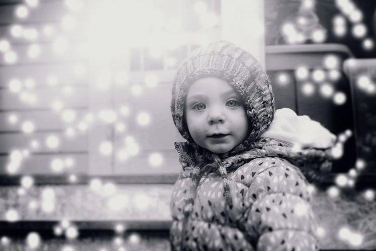 Portrait of cute girl against illuminated lighting equipment