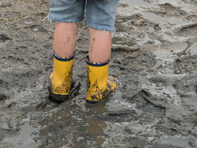 Beach Body Part Childhood Day Dirty High Angle View Human Body Part Human Foot Human Leg Human Limb Jeans Land Leisure Activity Lifestyles Low Section Mud Nature One Person Outdoors Real People Rubber Boot Shoe Standing Water