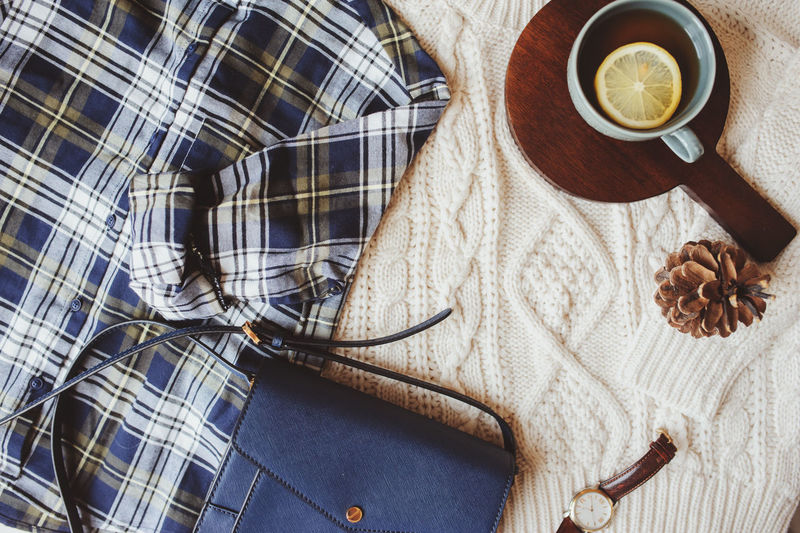 woman casual fall stylish clothes flat lay with plaid shirt, knitted sweater, cross body bag and cup of tea. Preparing for the walk in weekend. Autumn Fashion Morning Plaid Shirt  Bag Casual Clothing Cozy Cup Day Drink Fall Food Food And Drink High Angle View Hot Drink Indoors  Mug No People Outfit Still Life Table Tea Textile
