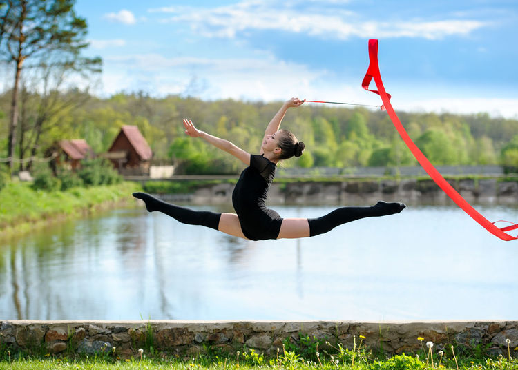 Acrobat Activity Brunette Caucasian Cheerful Fitness Girl Gymnastics Healthy Horizontal Jump Leg-split Outdoor Performance Ribbon Scene Skill  Split Sport Stretching