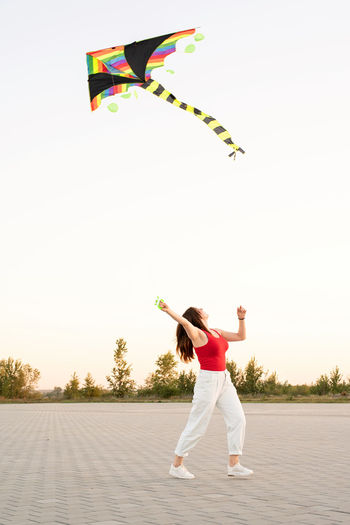 Full length of woman flying kite against sky