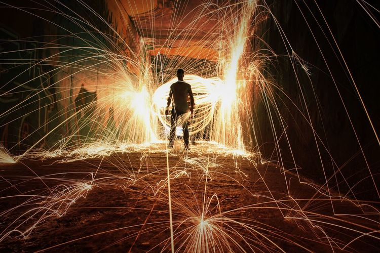 Rear view of man standing amidst wire wool