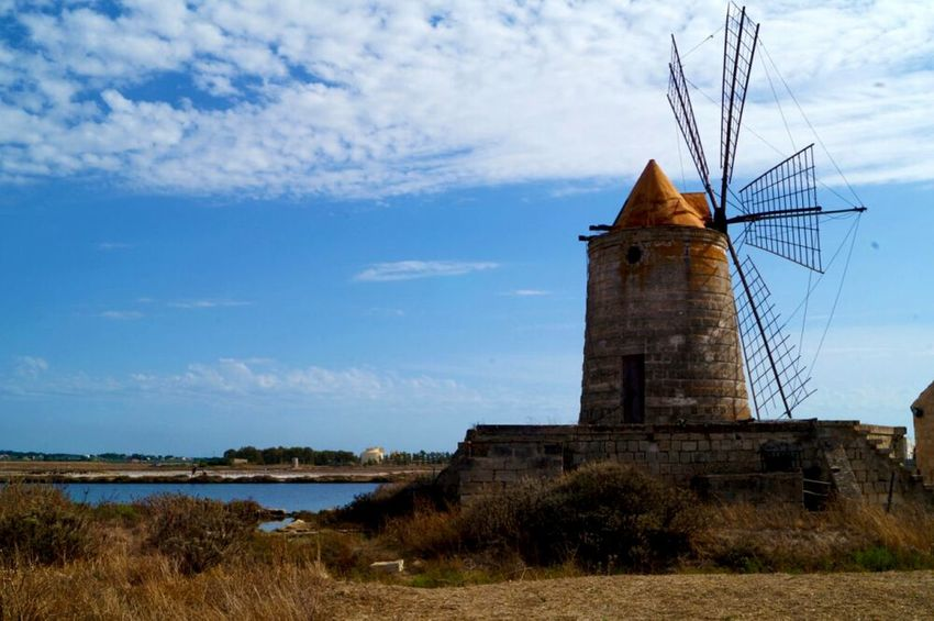 Old mill in SicilyMill Grass Old-fashioned Tower Windmill Water Nature Sky Building Exterior Architecture Outdoors No People Agriculture Vacations Day Cloud Blue Sky Donchisciotte Nature Silhouette Salt Sicily Sicilysummer Sicilia Saline Di Trapani