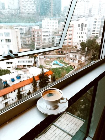 Coffee cup and buildings seen through glass window
