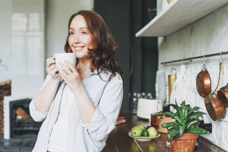 Woman holding coffee cup at home