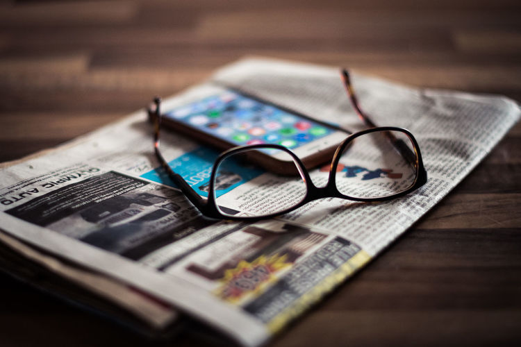 Close-up Day Eyeglasses  Eyesight Eyewear Glasses Indoors  Newspaper No People Smartphones Table Vision