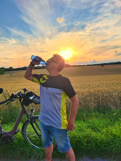 Full length of man holding bicycle on field against sky during sunset