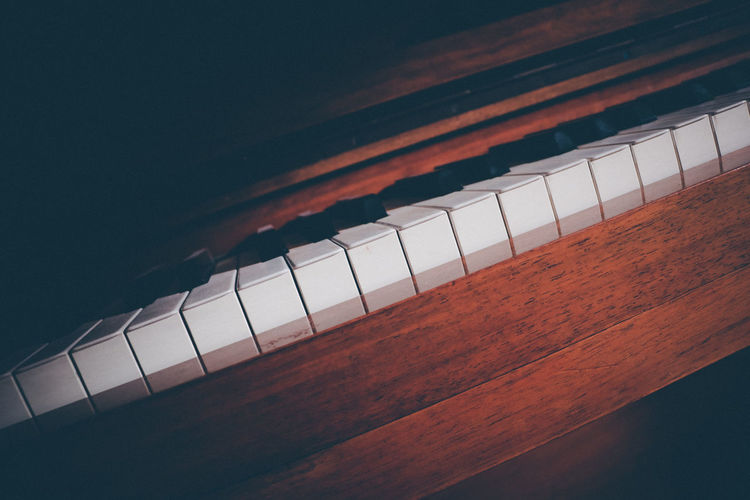 High angle view of piano keys on table against black background