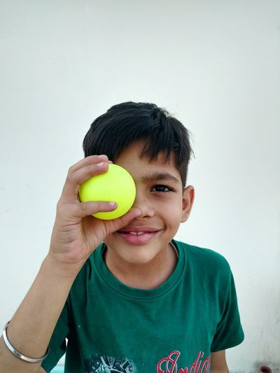 Portrait Of Happy Boy Holding Ball While Standing Against Wall