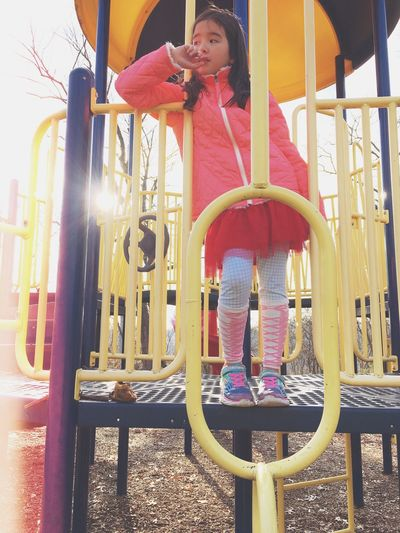 Thoughtful girl standing on outdoor playing equipment
