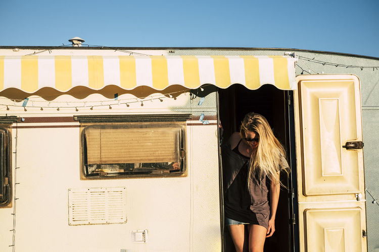 Old style american concept with beautiful blonde young girl on the door of a vintage old caravan - diversity and alternative travel style and vacation holiday adventure - freedom and tiny house One Person Real People Lifestyles Leisure Activity Young Adult Women Adult Standing Front View Casual Clothing Sunlight Day Built Structure Building Exterior Nature Young Women Architecture Three Quarter Length Hairstyle Blonde Beautiful Gil Caucasian Camper Caravan Old Vintage Outdoors Females Holiday Vacations Adventure Old Style American