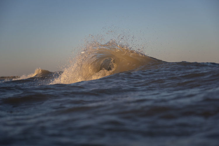 Waves splashing in sea against clear sky at sunset