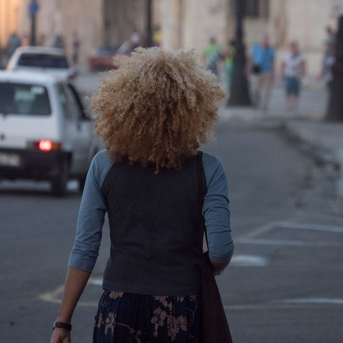 Malecón before sunset: Curly hair Afternoon Sunlight Close-up Cuba Cuba Collection Curly Hair Day Focus On Foreground Leisure Activity Lifestyles Malecon One Person Outdoors People Real People Rear View Tourist Attraction  Travel Photography Young Woman