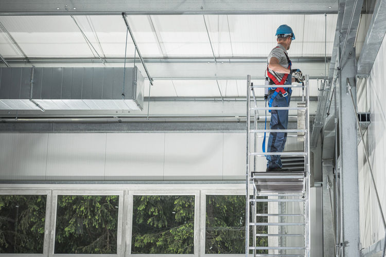 Man working while standing on scaffolding in building