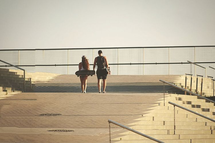 Man And Woman With Skateboards Walking On Steps