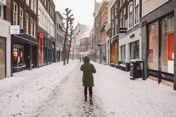 Rear view of man walking on snow covered street
