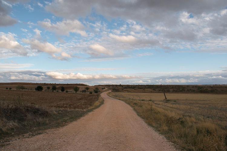 Dirt road amidst field against sky