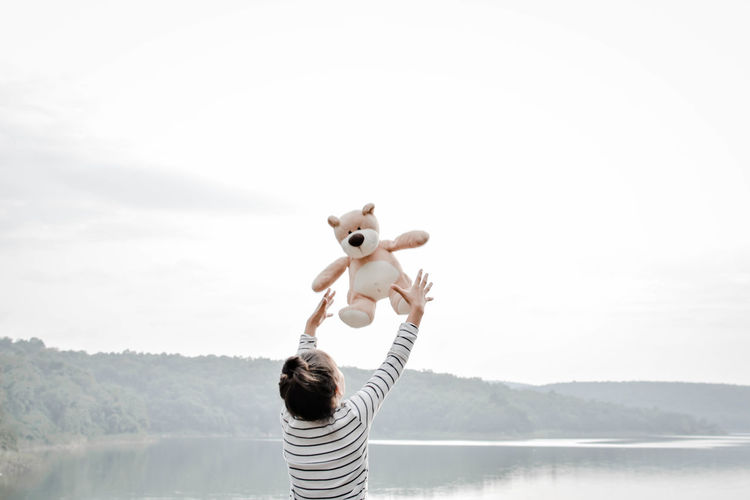 Rear view of girl playing with teddy bear by lake against clear sky