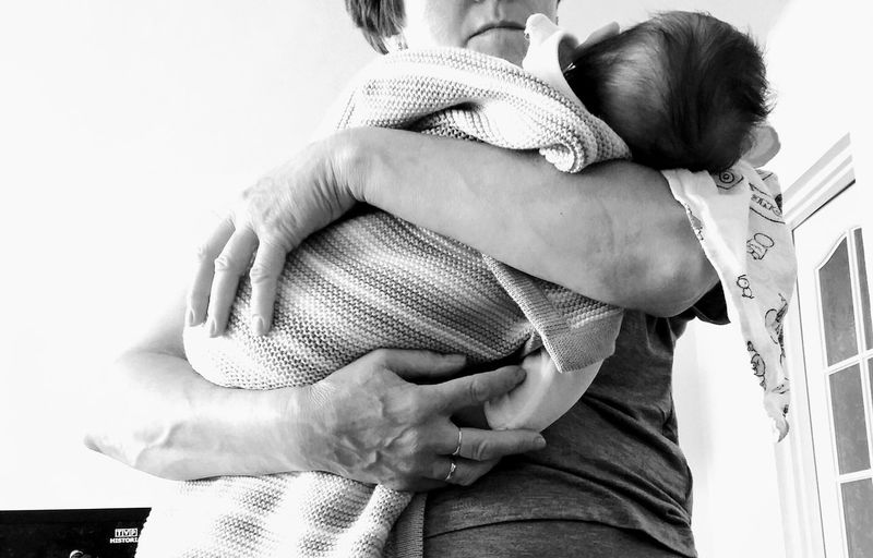 Midsection Of Mother Holding Baby Wrapped In Towel While Standing At Home