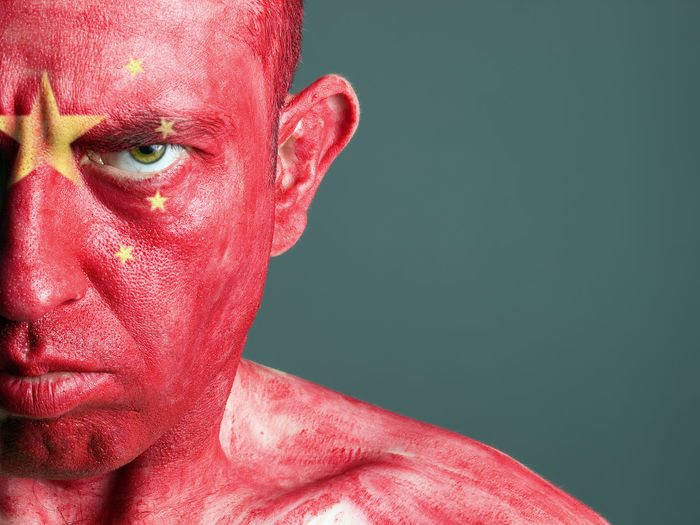 Close-up portrait of man with chinese flag body paint against gray background