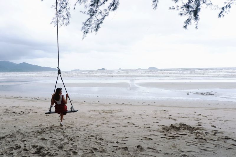 Rear view of woman sitting on swing at beach against sky