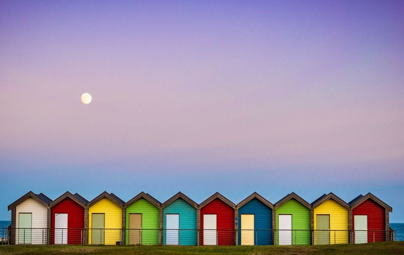 Multi colored beach huts against sky