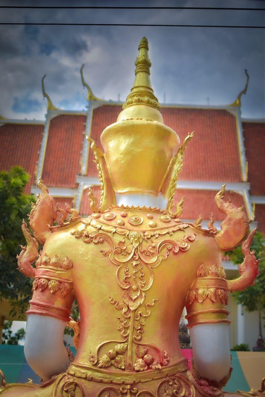 BUDDHA STATUE AGAINST BUILDING