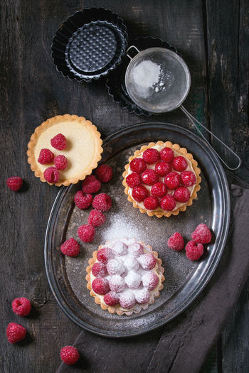 Unfinished and ready to eat tartlets with custard, sugar powder and fresh raspberries, served on vintage metal tray with baking forms and sieve over old wooden table. Dark rustic style. Flat lay Breakfast Shortbread Tart Tartlette Bake Baked Pastry Item Bakery Berry Fruit Custard Dark Background Dessert Flat Lay Food Food And Drink Fruit Group Lemon Curd Raspberry Red Shortbread Tartlet Sweet Sweet Food Tart - Dessert Top View Wood - Material