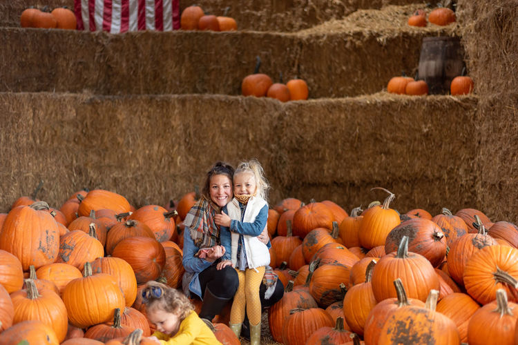Smiling mother and daughter standing amidst pumpkin